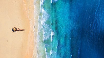 Aerial view of a girl on the beach. Beach and turquoise water. Top view from drone at beach, blue sea and relax girl. Travel and relax - image