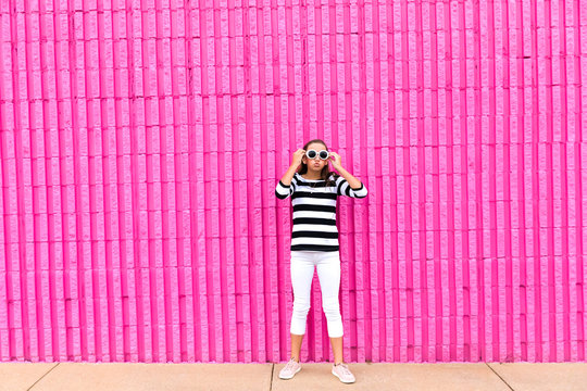 Cute caucasian girl celebrating her 13th birthday teenager standing in front of a hot pink wall outside holding her sunglasses