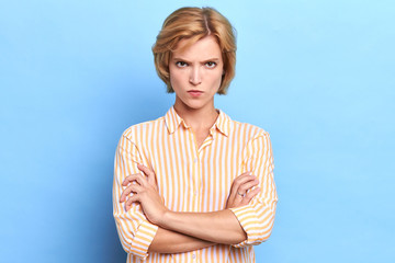 Angry unhappy sad woman looking at camera with sceptical and displeased expression, arms crossed. Portrait of beautiful female boss disappointed or angry with her office workers