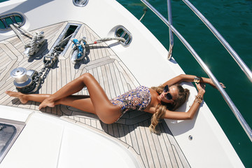 fashion outdoor photo of beautiful girl with blond hair in elegant beach clothes  and accessories posing on luxurious yacht