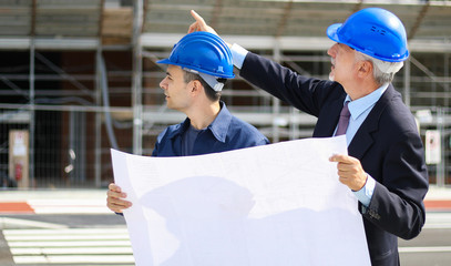 Two architect developers reviewing building plans at construction site