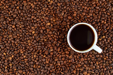 Background of roasted coffee beans. In the foreground is a white coffee Cup with coffee.