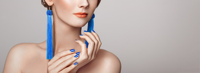 In de dag Manicure Beautiful woman with large earrings tassels jewelry blue color. Perfect makeup and nails manicure