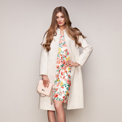 Young elegant woman in trendy white coat. Blond hair, floral dress, isolated studio shot. Fashion autumn lookbook. Model woman with handbag