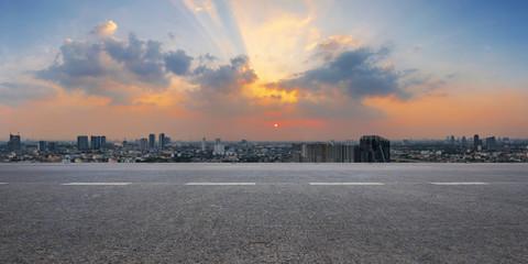 Fotomurales - Empty highway asphalt road and city skyline at sunrise background