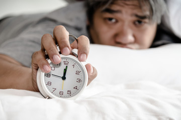 Asian middle aged man just waking up looking at the alarm clock Held in the hand, on white bed in the bedroom, concept to was not enough rest time and This picture focuses on alarm clock