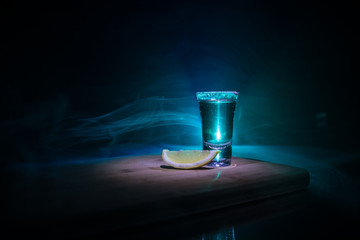 Club drink concept. Tasty alcohol drink cocktail tequila with lime and salt on vibrant dark background or glasses with tequila at a bar