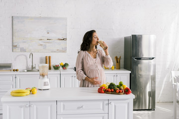 pregnant woman drinking smoothie near table with tasty food
