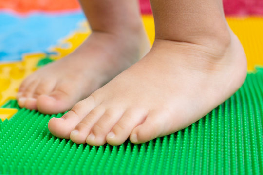 treatment and prevention of flat feet in children. A small child walks barefoot on an orthopedic mat puzzle. Gymnastics for feet are useful for the whole body