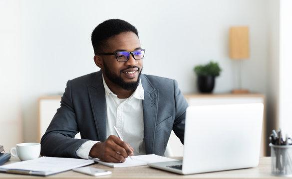 Handsome black entrepreneur working on laptop and taking notes