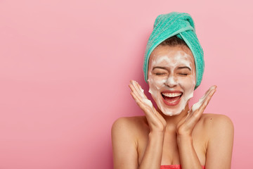 Happy joyous young girl spreads palms over face, washes face with soap, has fun in bathroom, pampers skin, wears wrapped towel on head, expresses positive emotions, poses against pink background