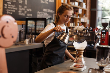 Professional barista preparing coffee using chemex pour over coffee maker and drip kettle. Young woman making coffee. Alternative ways of brewing coffee. Coffee shop concept.