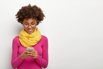 Horizontal shot of pleased dark skinned female holds modern mobile phone, focused into display, wears pink turtleneck, sends pictures online, browses internet page, stands against white wall