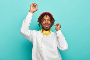 Upbeat carefree mixed race guy dances with hands up, listens awesome music track via headphones, has dreads, wears white comfortable jumper and stylish hat, isolated on blue. Time for fun and relax