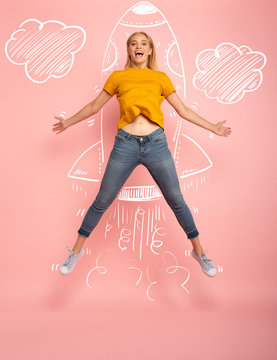 Girl jumps on pink background ready to fly like a rocket. Concept of freedom, energy and vitality