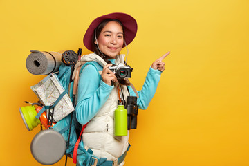 Active female backpacker points index finger on copy space aside, holds retro camera, takes pictures, carries rucksack, binoculars and thermos, wears casual clothes, isolated over yellow background