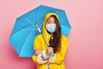 Photo of surprised brunette Asian woman wears medical mask, being protected from catching disease, wears yellow raincoat, holds umbrella, walks in rainy weather on street, has shocked expression