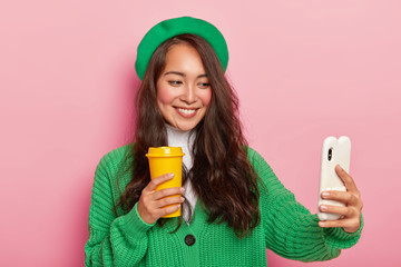 Happy moments must be photographed. Cheerful mixed race lady in green beret and knitted sweater, makes selfie portrait with cell phone, poses with coffee cup against pink background, smiles pleasantly