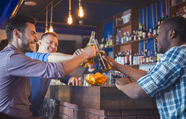 Happy Guys Clinking Beer Bottles In Bar