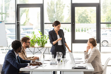 multiethnic businesspeople sitting at tables during conference in office Wall mural