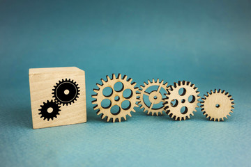 four wooden gears and one gear on a cube on a blue background.