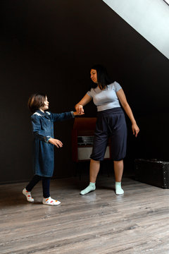 Mom and daughter dancing together in the dark room
