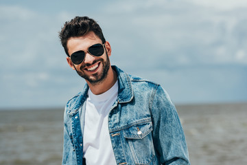 Fotomurales - handsome man in denim jacket and sunglasses looking at camera