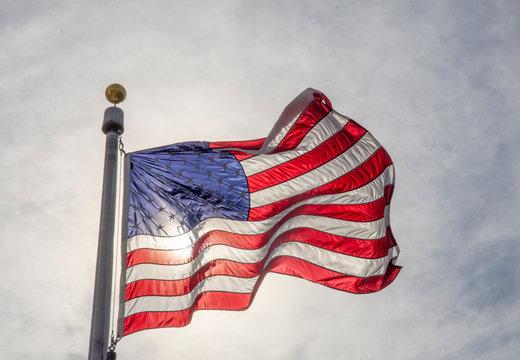 Sun shines through a U.S. flag on the grounds of the Washington Monument in Washington, DC.