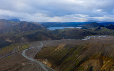 Iceland in september 2019. Great Valley Park Landmannalaugar, surrounded by mountains of rhyolite and unmelted snow. In the valley built large camp. The concept of world tours.