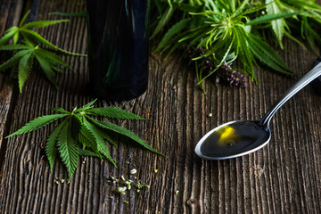 Cannabis oil in the spoon on the wooden background, cannabis leaves with blossoms and black bottle with cannabis oil on the table, healthy food concept