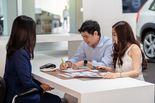 Asian couple signing the contract with saleswoman after decision the buy the new car in showroom, Customer service and sales representative concept