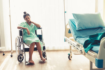 Serious patient sitting on wheelchair in hospital ward. Bad health result make the patient unhappy. Medical malpractice concept.
