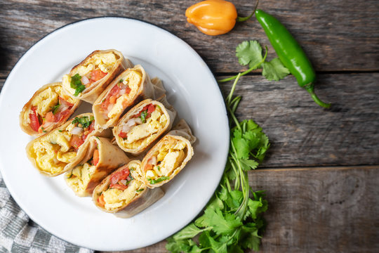Mexican egg burritos with fresh sauce on wooden background