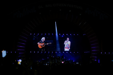 May of Queen is seen on screen with a projection of Mercury as he performs onstage at the 2019 Global Citizen Festival at Central Park in New York