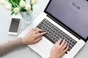 Woman hand MacBook Pro with social networking service Google