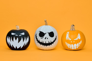 Three Spooky Halloween pumpkins with scary face expressions over orange background. Halloween...