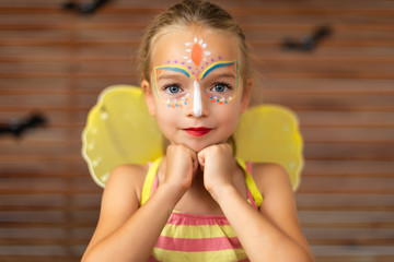 Waist up portrait of cute preschooler with DIY face paint wearing a butterfly halloween or carnival...