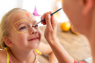 Young mother painting daughters face for Halloween party. Halloween or carnival family lifestyle...