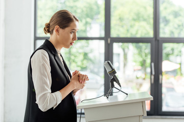 side view of attractive businesswoman standing during conference in conference hall