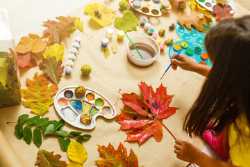 Girl paints leaves. Gouache, brush and various autumn leaves, Children's art project. Colorful Hand-painted on dry autumn leaves