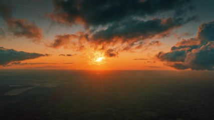 Fotobehang - Aerial view of epic dark clouds flying into camera, revealing scenic sunset sun setting into horizon. Timelapse, 4K UHD.