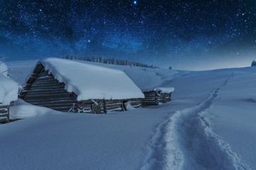 Fairytale landscapes of the winter Carpathian Mountains with a charming milky way in the sky tourist tents and snowy houses in the valleys