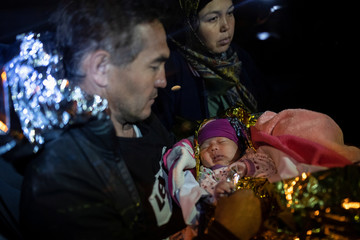 A migrant couple from Afghanistan hold their 20-day-old baby, as they are transferred on a minibus following a rescue operation by the Greek Coast Guard, in Skala Sikamias, on the island of Lesbos