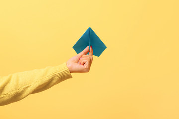 Wall Mural - Woman hand holding blue paper airplane over yellow background, freedom concept.