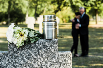 selective focus of white flowers and cemetery urn on tombstone