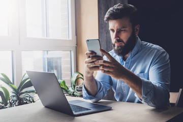 Office worker relaxing, playing online games on smartphone. Man downloading interesting apps on his mobile device. Home-based freelancer looking for instructions on its work. Male adult checking email