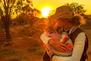 Tourist man holding orphaned baby kangaroo at sunset sunlight in Australian outback. Interacting with cute kangaroo orphan. Australian Marsupial in Northern Territory, Central Australia, Red Centre.