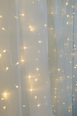 blurred led light wall garland on white tulle fabric backdrop, festive decoration, vertical stock photo image background