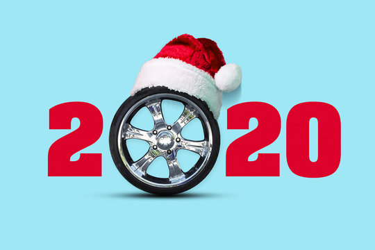 2020. Auto wheel instead of zero. Santa hat. Isolated on blue background. New Year background.
