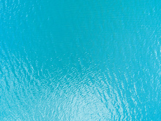 Aerial view of a Crystal clear sea water texture. View from above Natural blue background. Turquoise ripple water reflection in tropical beach. Blue ocean wave. Summer sea. Drone. Top view